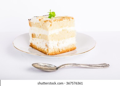 Serving cake with a creamy cream and nuts isolated on white background
