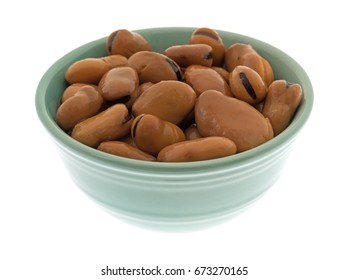 A serving of canned fava beans in a small green bowl isolated on a white background.