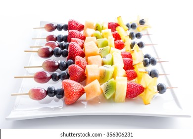 Serving of colorful fresh tropical fruit kebabs on a modern rectangular white plate viewed low angle with receding perspective on white