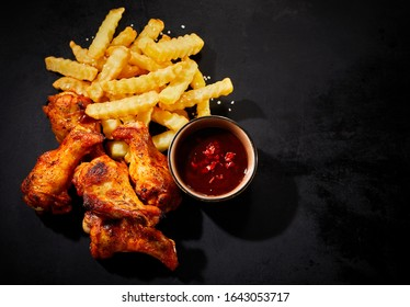 Serving of crispy spicy grilled chicken wings with a chili dip on the side and crinkle cut French Fries or potato chips viewed from above on a dark slate with copy space