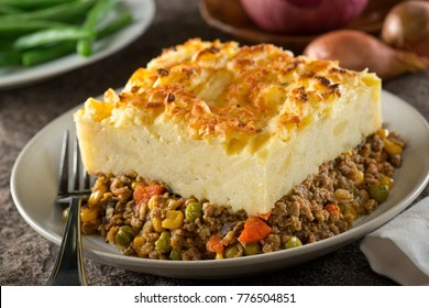 A serving of delicious homemade shepherd's pie with ground meat, mashed potato, carrots, peas, corn, and cheddar cheese crust.