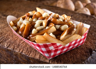 A serving of delicious poutine with french fries, cheese curds and gravy on a rustic wooden board.