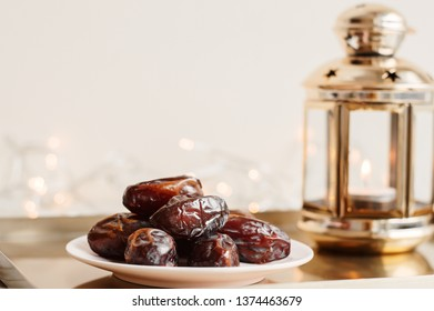 Serving of dried dates and gold colored lantern on metal tray, festive lights as background. Ramadan month