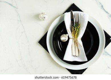Serving of the Easter table with cutlery, Easter bunny and a twig of mimosa in black and white tone in the marble table. Holiday background. Top view.Copy space