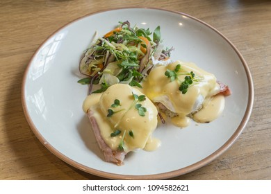 A serving of Eggs Benedict. A popular breakfast consisting of a poached egg with bacon on a muffin with hollandaise sauce.