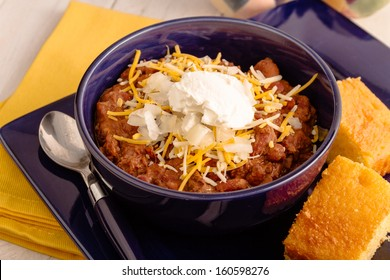 Serving of elk meat chili with red beans, sour cream, shredded cheese and diced onions in blue bowl and cornbread side
