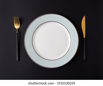 Serving empty plate with tableware at black background