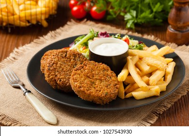 Serving of falafel and chips served on a black plate with sauce. Front view.