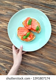 Serving food: breakfast toasts with garden tomatoes and fresh basil. Top view, eating healthy. Home made recipe. Easy meal. Snack or appetizer.Sprinkled with coarse sea salt. Wooden kitchen table.