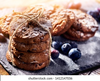 Serving food on slate onto wooden table. Oatmeal cookies biscuit with blueberry on picnic dark tiles countrylike. Chocolate chip cookies tied with string sun flare.