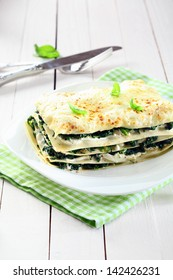 Serving of fresh baked vegetarian spinach lasagna on a plate over a napkin and an old white wooden table