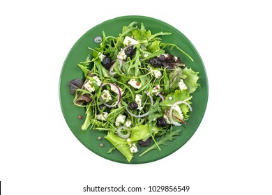 Serving of fresh Greek salad with leafy greens, herbs, tomato, feta and olives on a whites background