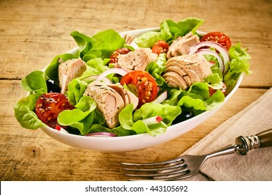 Serving of fresh tuna salad with lettuce, tomato, olives and onion in a white bowl on a rustic wooden table with fork and napkin, high angle view