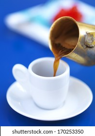 serving greek coffee on a bright blue table