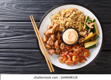 Serving hibachi of rice, shrimp, steak and vegetables served with sauce closeup in a plate on the table. Horizontal top view from above