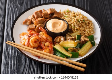 Serving hibachi of rice, shrimp, steak and vegetables served with sauce closeup in a plate on the table. horizontal