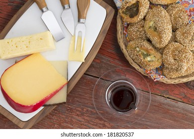 Serving of manchego,, gouda and havarti cheese on a cheeseboard with cutters and a glass of red wine alongside a basket of delicious fresh sesame pastries, overhead view on a rustic table