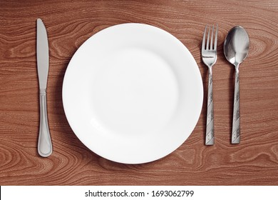 serving metal cutlery lie on a wooden table next to a plate