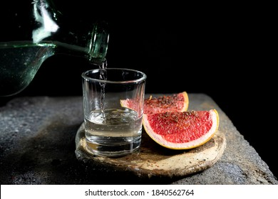 SERVING MEZCAL WITHIN A GLASS ON A RUSTIC PLATE AND GRAPES, ON A BLACK BACKGROUND