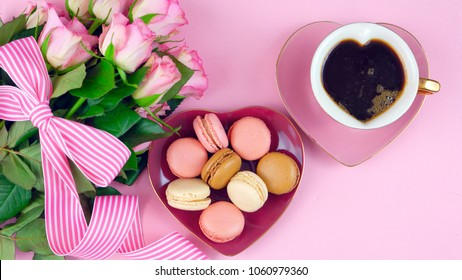 Serving Mother's Day coffee and macarons with roses gift overhead on pink wood table background.