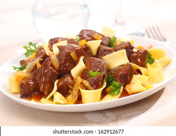 Serving on a plate of beef goulash, a stew that originated in Hungary, served with noodles and garnished with fresh chopped parsley