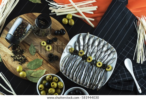 Serving on the table of the delicious little fish sprat, condiments, olives and decor. The view from the top