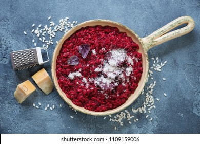 Serving pan with beetroot risotto and grated parmesan cheese, view from above on a blue stone background, horizontal shot