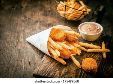 Serving in a paper cone of takeaway crumbed fried fish nuggets with potato chips and a small bowl of sauce or dip on a rustic wooden table with copyspace