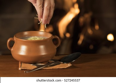 Serving Parmesan Cheese on a Bowl of Warm Soup / Hand serving parmesan cheese on a bowl of warm soup with a fireplace on the background