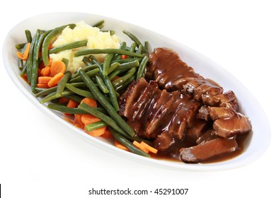 Serving platter of sliced roast beef and gravy, with vegetables.  Isolated on white.