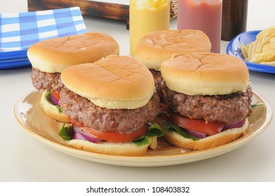 a serving platter of thick hamburgers with condiments