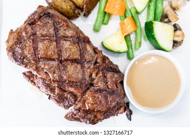 Serving portion of delicious grilled wagyu beef steak with side dishes and sauces