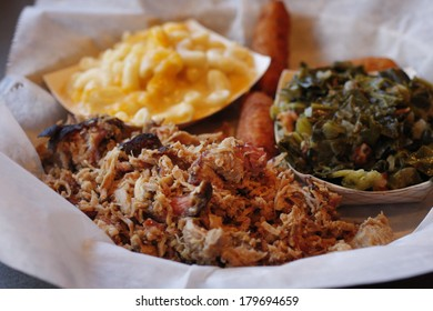 A serving of pulled pork with side dishes of Macaroni and cheese,  collard greens, and fried hush puppies.