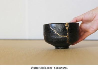Serving a repair of crack pottery tea cup  / horizontal