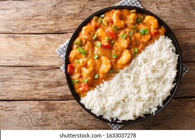 Serving of shrimp Etouffee with vegetables and sauce served with rice closeup in a plate on the table. Horizontal top view from above