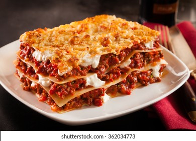Serving of spicy traditional Italian beef lasagne in a restaurant on a modern white square plate with a red napkin, dark counter background