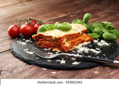 Serving of spicy traditional Italian beef lasagne in a restaurant - bolognese sauce topped with basil leafs
