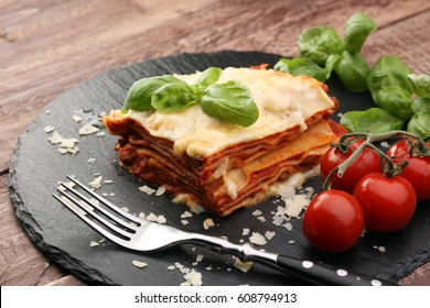 Serving of spicy traditional Italian beef lasagne in a restaurant - bolognese sauce topped with basil leaves