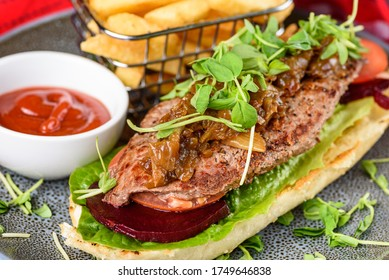 A serving of Steak Sandwich with Beetroot, Lettuce and a side of French Fries and Tomato Sauce