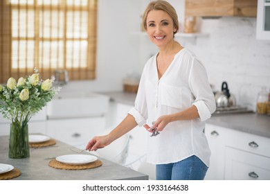 Serving the table. Blonde housewife in shirt and jeans serving the table for dinner