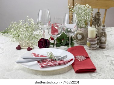 Serving, table decoration Valentine's Day. Table set, napkins with hearts, decorative homemade bottles, candle and rose.