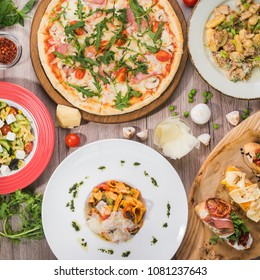 Serving table for lunch from pizza, pasta, bruschetta on a wooden background. Food set, top view.