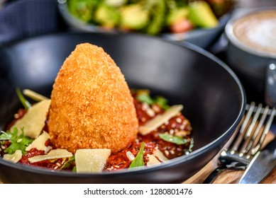 A serving of traditional Italian Arancini with Parmesan cheese