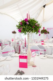 Serving wedding table to celebrate the event with glasses and plates in the restaurant for guests. Decoration with natural flowers and candles