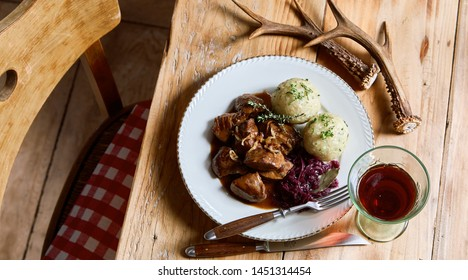 Serving of wild venison goulash and dumplings with shredded red cabbage and a glass of red wine on a rustic table set with deer antlers viewed high angle
