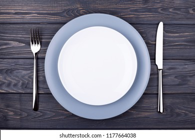 Serving wooden table with empty plate, fork and knife. Top view.