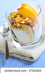 Serving of yogurt with fresh peaches and granola