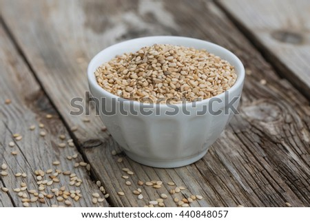 Sesam seeds in a little bowl on wooden table. Natural light. Selective focus.