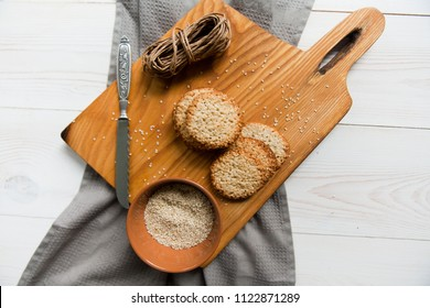 sesame biscuits, a plate of sesame, knife, rope on the wooden board,lying on the white wooden background. Top view. Free space for text.