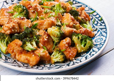 Sesame Chicken And Broccoli In Blue Plate. View From Above, Top Studio Shot